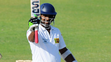 Dilruwan Perera raises his bat after scoring a maiden Test fifty