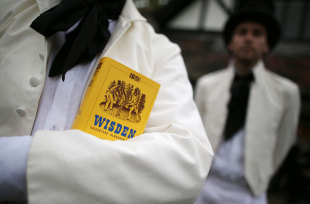 A team member holds a copy of the <i>Wisden Cricketers' Almanack</i> during a Victorian cricket match, Vincent Square, London, May 29, 2013