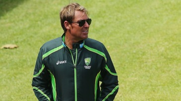 Shane Warne walks along the boundary line