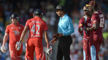 The umpire intervenes to break-up an argument between players