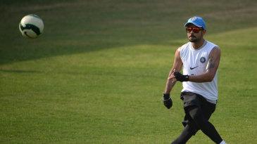Virat Kohli kicks about a football during a practice session