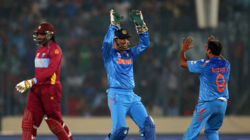 MS Dhoni and Amit Mishra celebrate the run-out of Chris Gayle