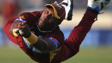 Dwayne Bravo dives full length to pluck a chance