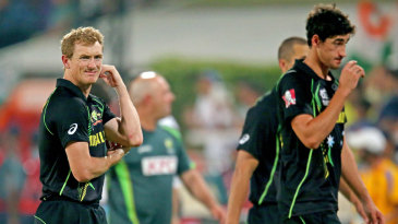 A dejected George Bailey and Mitchell Starc walk off the field