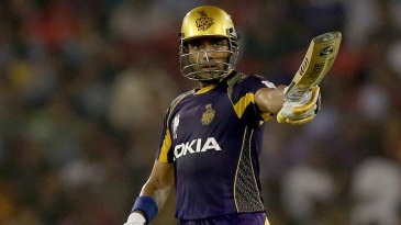 Robin Uthappa raises the bat after reaching his fifty
