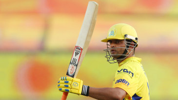 Suresh Raina raises the bat after reaching his fifty