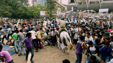 A policeman tries to disperse the crowd outside Eden Gardens
