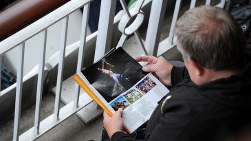A cricket fan reads a magazine