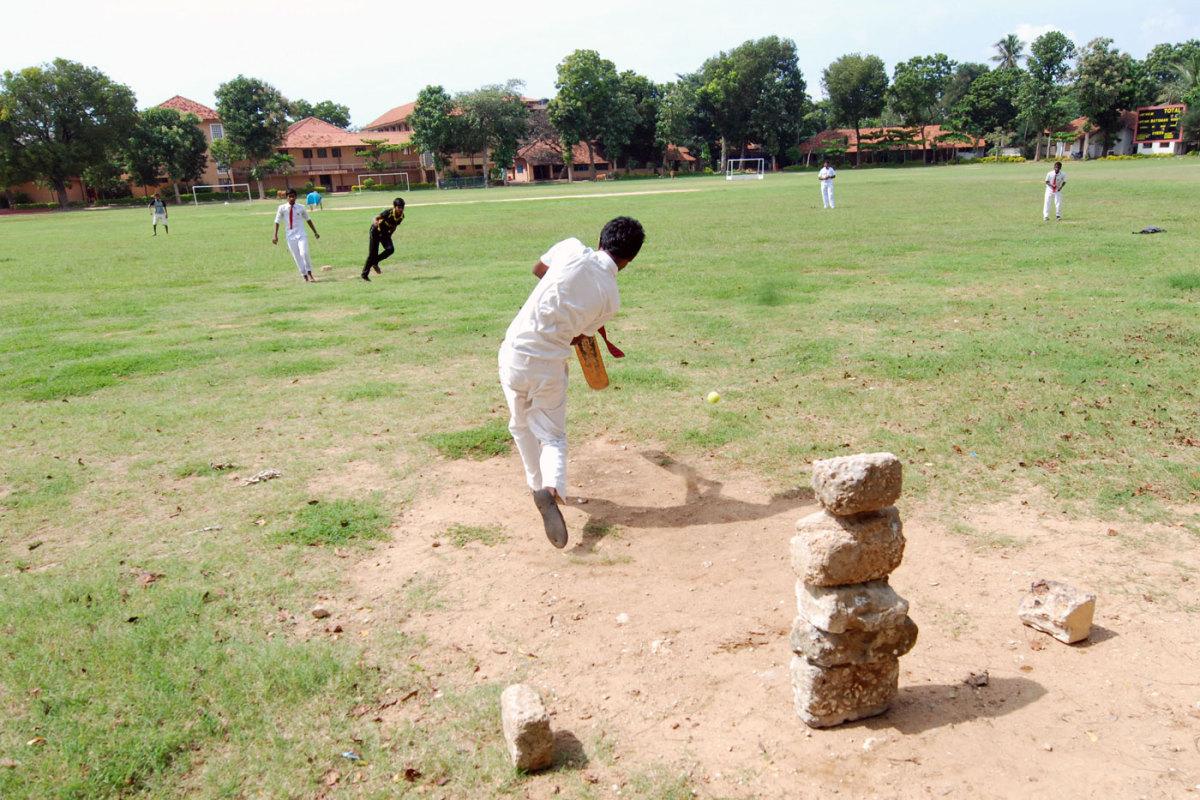 School children play cricket at the St John's ground