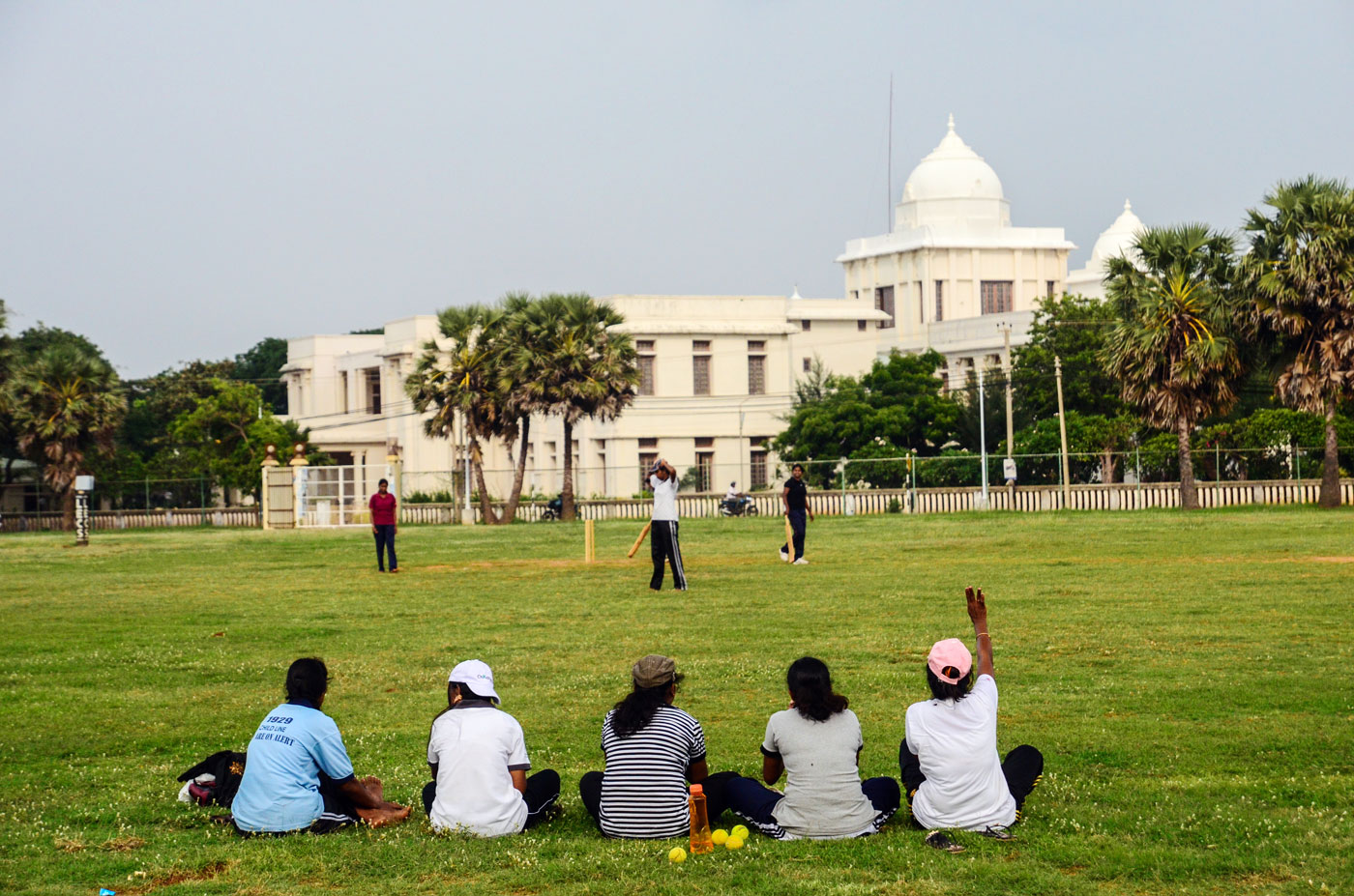 Girls play a cricket match at a ground overlooking the Jaffna library