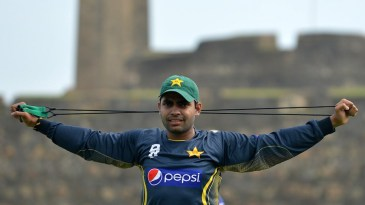 Umar Akmal stretches during a practice session