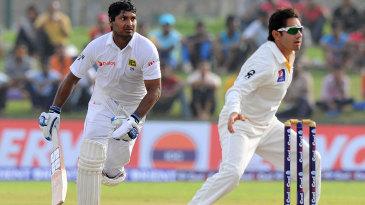 Drama: Kumar Sangakkara strives to make his ground before Saeed Ajmal gets the ball