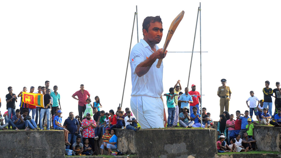 Spectators gather to watch the final day's play next to a cut-out of Mahela Jayawardene