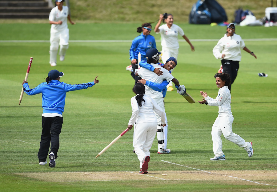 The India players run to the pitch to celebrate their win