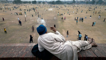 A man watches dozens of simultaneous games of cricket at Lahore's Iqbal Park