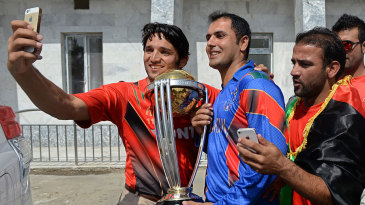 Fans grab the chance for a photo with Mohammad Nabi and the World Cup