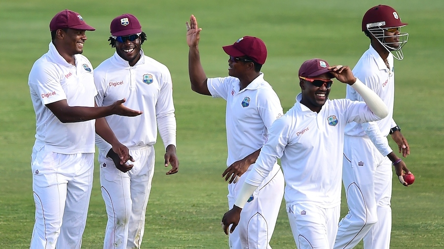 West Indies players celebrate the fall of a wicket