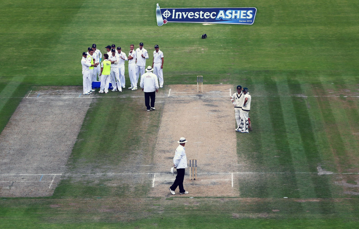 The England players wait for a review against David Warner