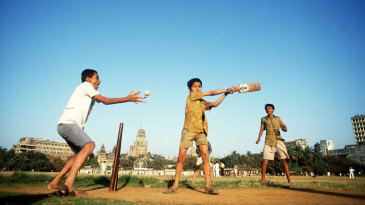 Kids play cricket in a maidan in Mumbai