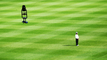 Umpire Asad Rauf stands with th Spidercam hovering above