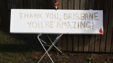 A sign in mud outside a home in the St Lucia suburb in Brisbane as the recovery work after the floods begins