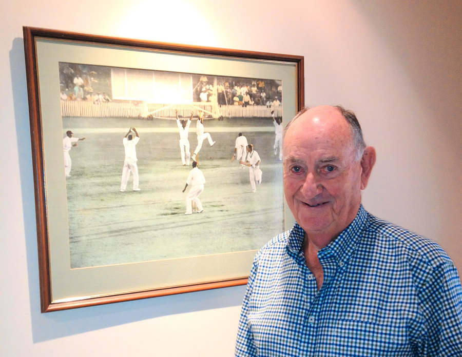 Living history: Meckiff poses next to the famous photograph of the 1960 tied Test, where he was the last man out
