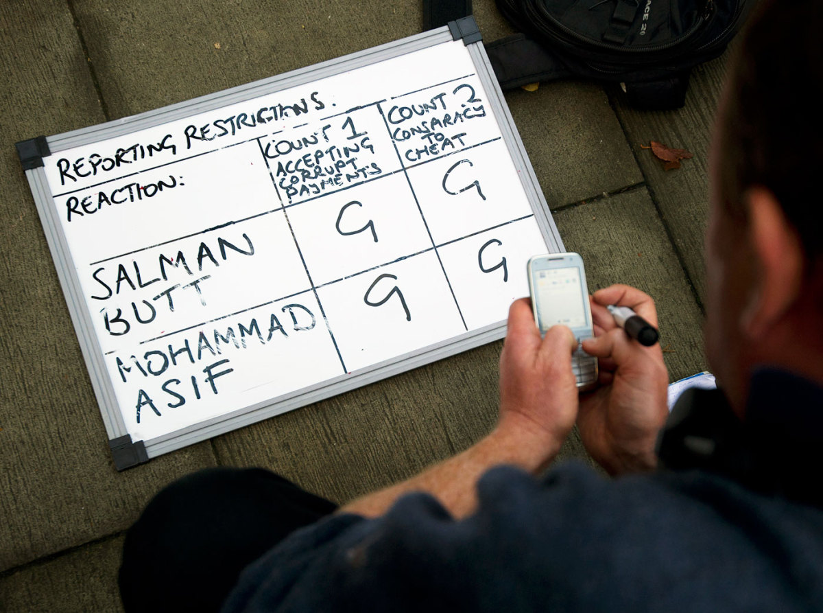 A reporter waits for a text update next to whiteboard indicating guilty verdicts for Salman Butt and Mohammad Asif outside the Southwark Crown Court in London