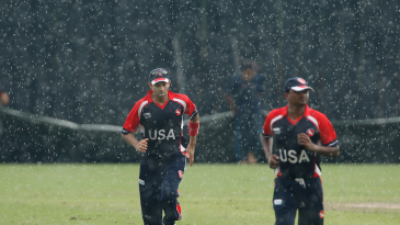 The USA players run back during a rain interruption