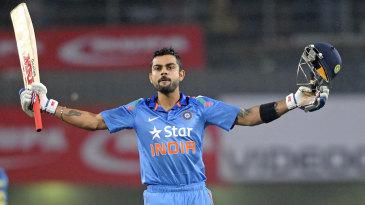 Virat Kohli raises his bat after reaching a century
