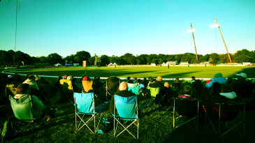 Spectators watch the T20 under temporary lights