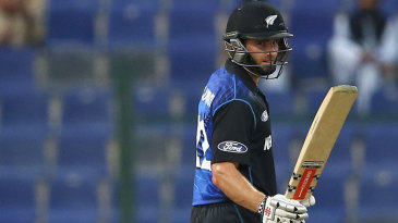 Kane Williamson raises his bat after reaching fifty