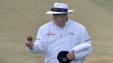 Umpire Steve Davis looks at the ball before changing it