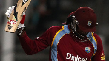 Chris Gayle holds up his bat on passing 50