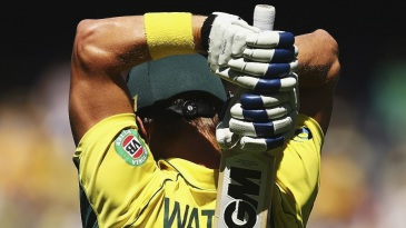 Shane Watson stretches his arms as he walks out to bat