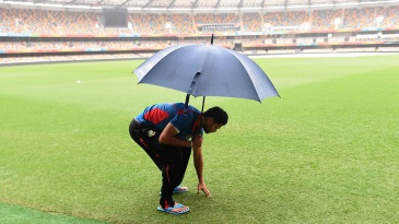 Mashrafe Mortaza inspects the wet outfield at the Gabba