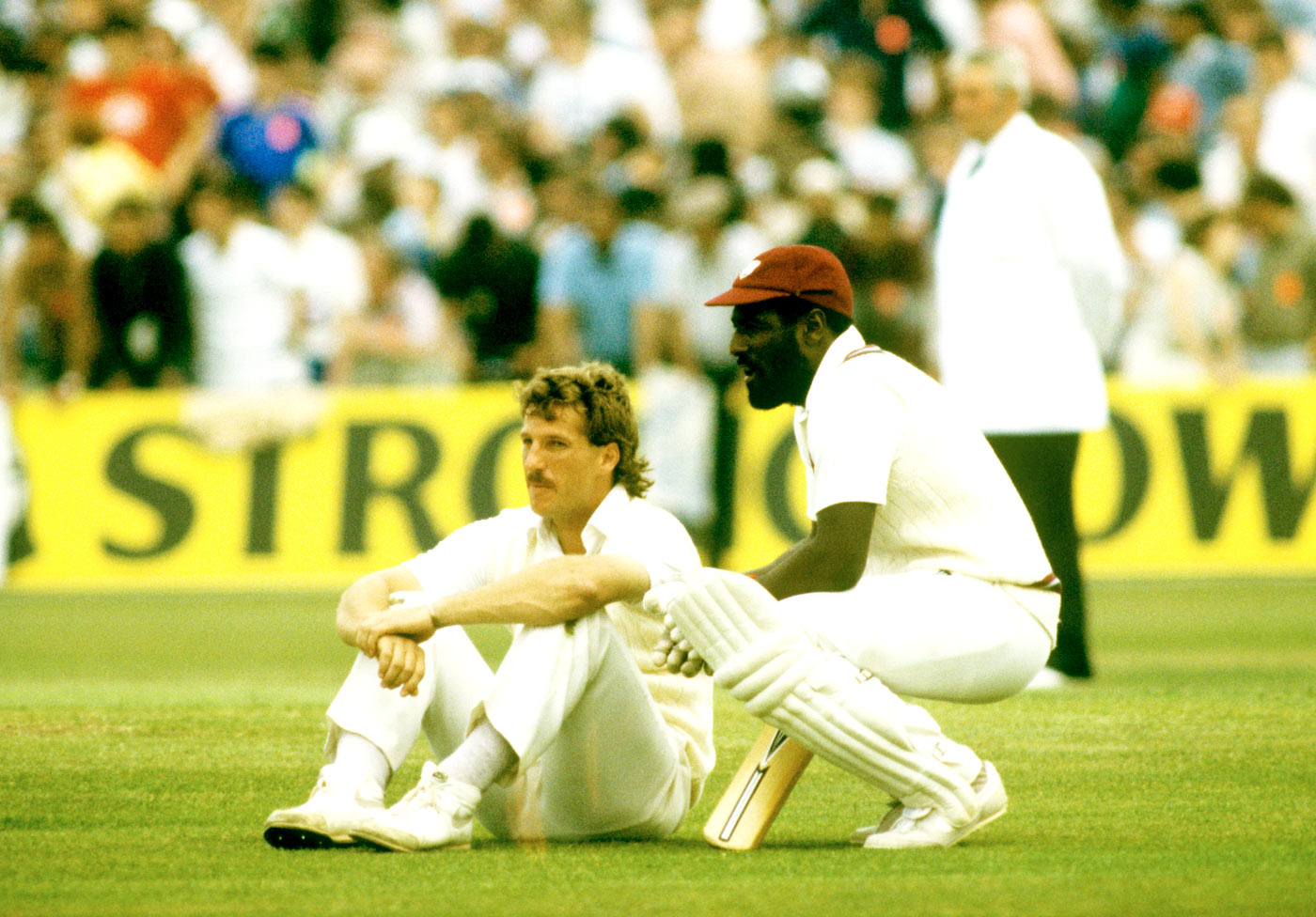 I wouldn't want to bowl to me either: a defeated Botham sits on the field next to Richards during the Old Trafford innings