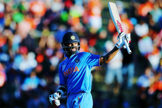 Shikhar Dhawan raises his bat after his fifty