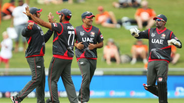 UAE players celebrate the fall of a wicket