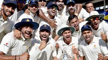 The Karnataka players celebrate after retaining the Irani Cup