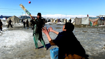 Afghan kids play cricket in a refugee camp in Kabul
