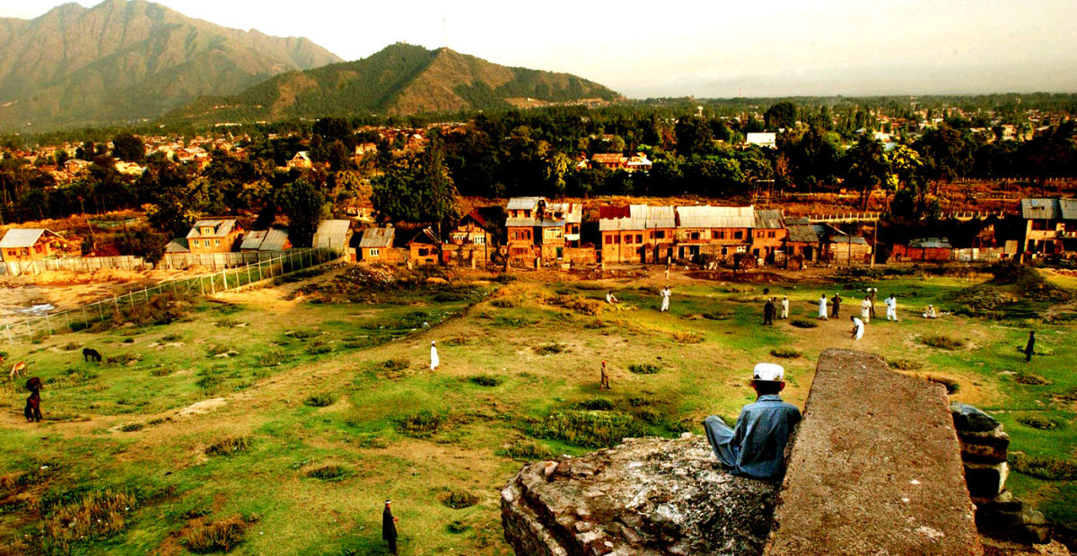 A boy sits on top of a crumbling structure and watches his classmates play cricket
