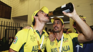 Left-arm over: Mitchell Starc guzzles a drink offered by Mitchell Johnson