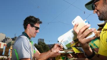Mitchell Starc signs autographs