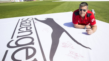 Ashley Giles signs a flag to mark James Anderson's record wicket haul