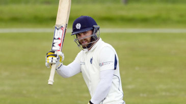 Scotland captain Preston Mommsen raises his bat after reaching 50