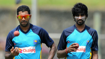 Dhammika Prasad and Nuwan Pradeep wait for their turn to bowl