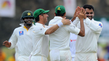 Mohammad Hafeez is mobbed by his team-mates after dismissing Lahiru Thirimanne
