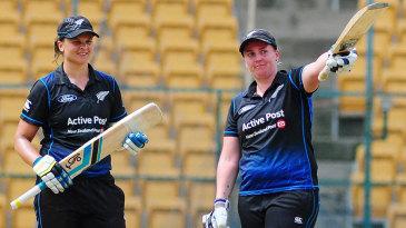 Rachel Priest raises her bat after scoring a half-century