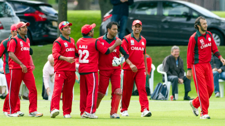 The Oman players get together after a wicket