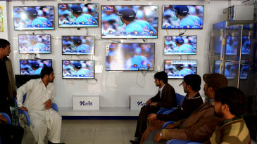 Pakistani shopkeepers watch the live broadcast of the India-Pakistan World Cup match at a market in Rawalpindi